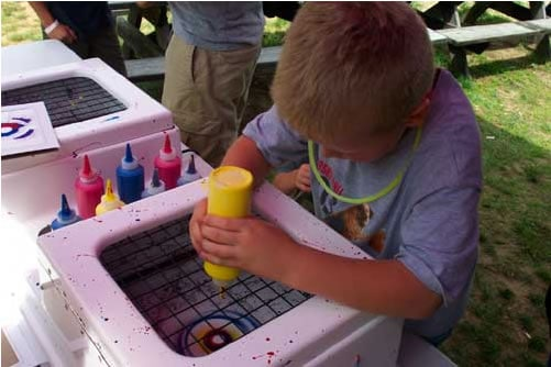 Boy creating T-shirt using spin art